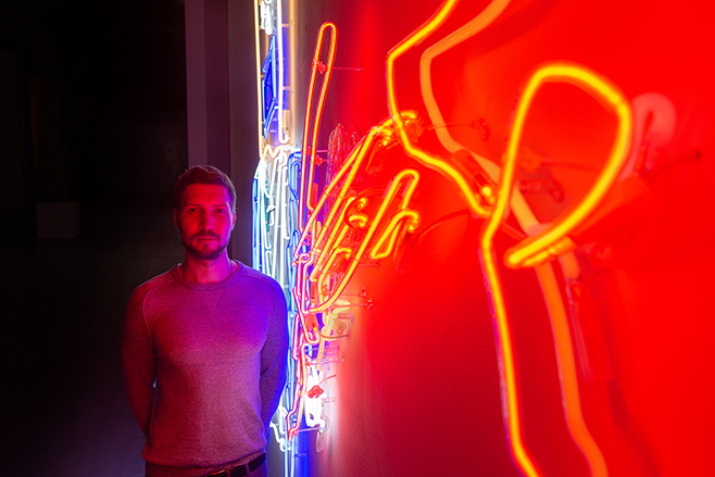 "Stepan Ryabchenko near his ""War and Peace"" neon installation in Art Arsenal / Photo: Maxim Belousov"
